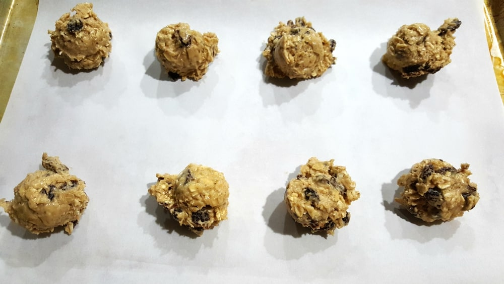 8 unbaked oatmeal cookies on parchment paper on a baking sheet
