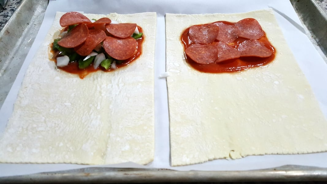 two puff pastry rectangles with pizza sauce, pepperoni, green pepper, and onion