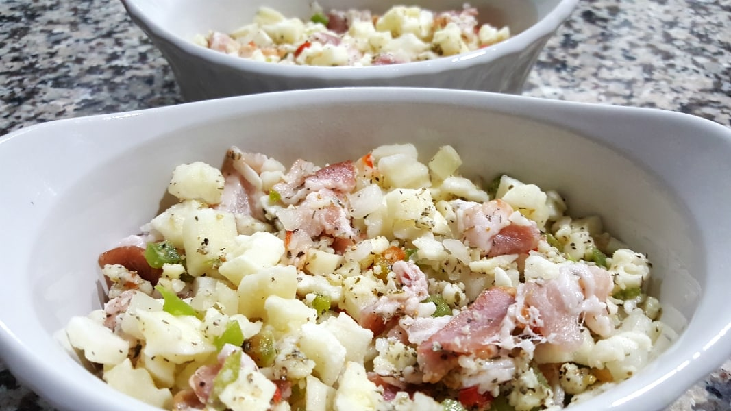 hashbrown potatoes, herbs, and bacon in two baking dishes