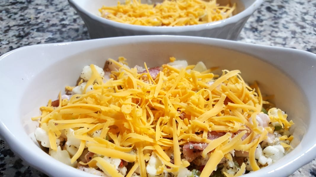 hasbrown mixture topped with cheese in two baking dishes