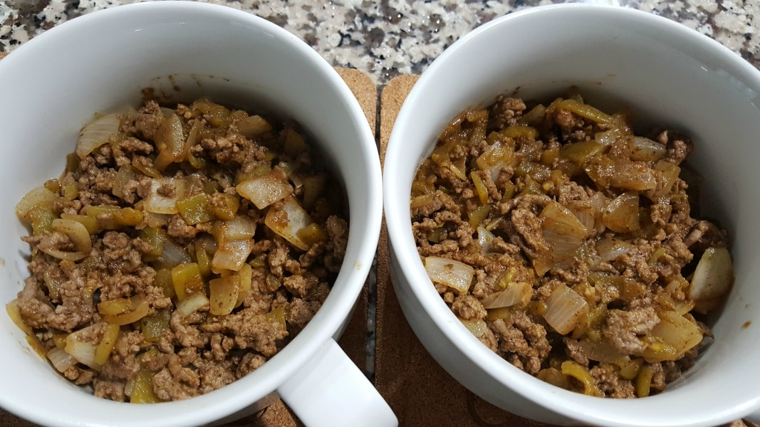 two round baking dishes filled with ground beef, garlic, green chiles, cumin, oregano, and chili powder