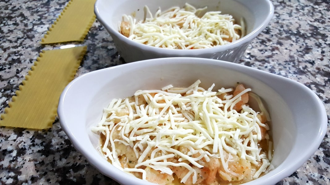 two baking dishes have shrimp topped with white shredded cheese