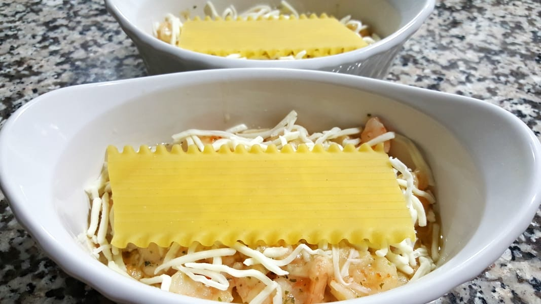 two baking dishes, shrimp and cheese topped with lasagna noodle