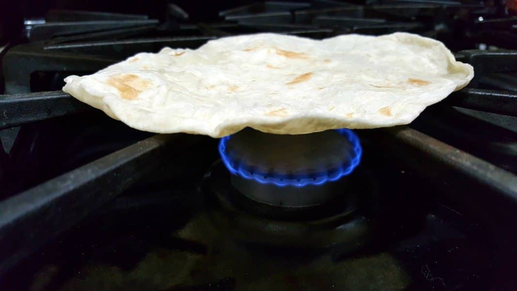 a tortilla shell on a stove top with a flame under it