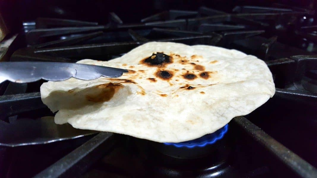 a pair of tongs with a tortilla over a flame on a stove top