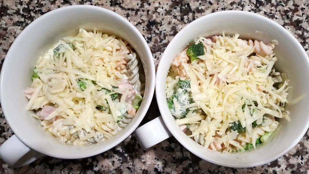 two oven safe dishes filled with cheesy ham broccoli casserole and topped with shredded cheese