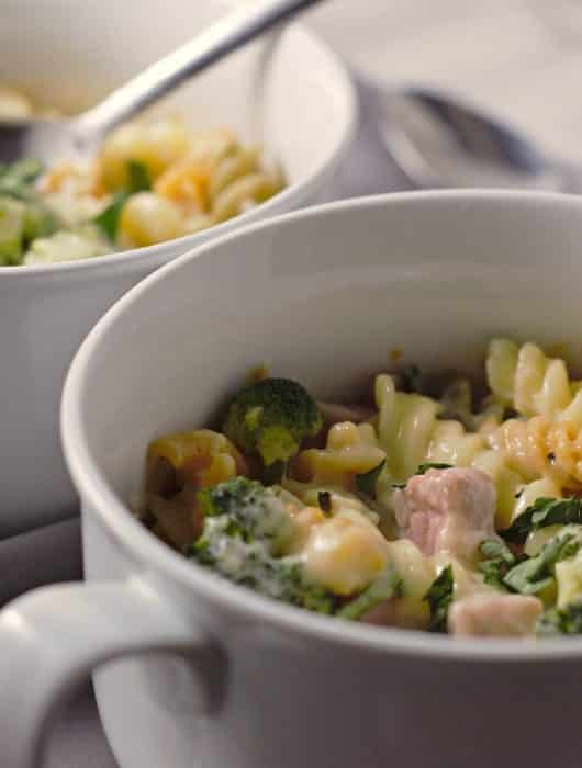 two oven safe dishes filled with cheesy ham broccoli and one has a spoon in it