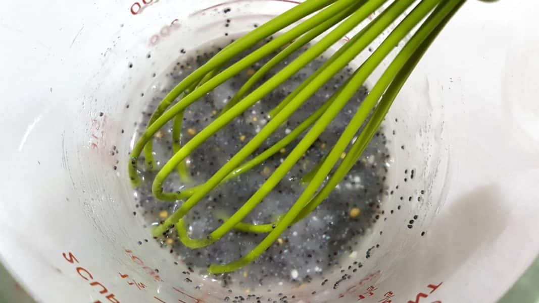 poppy seed dressing in a bowl with a whisk