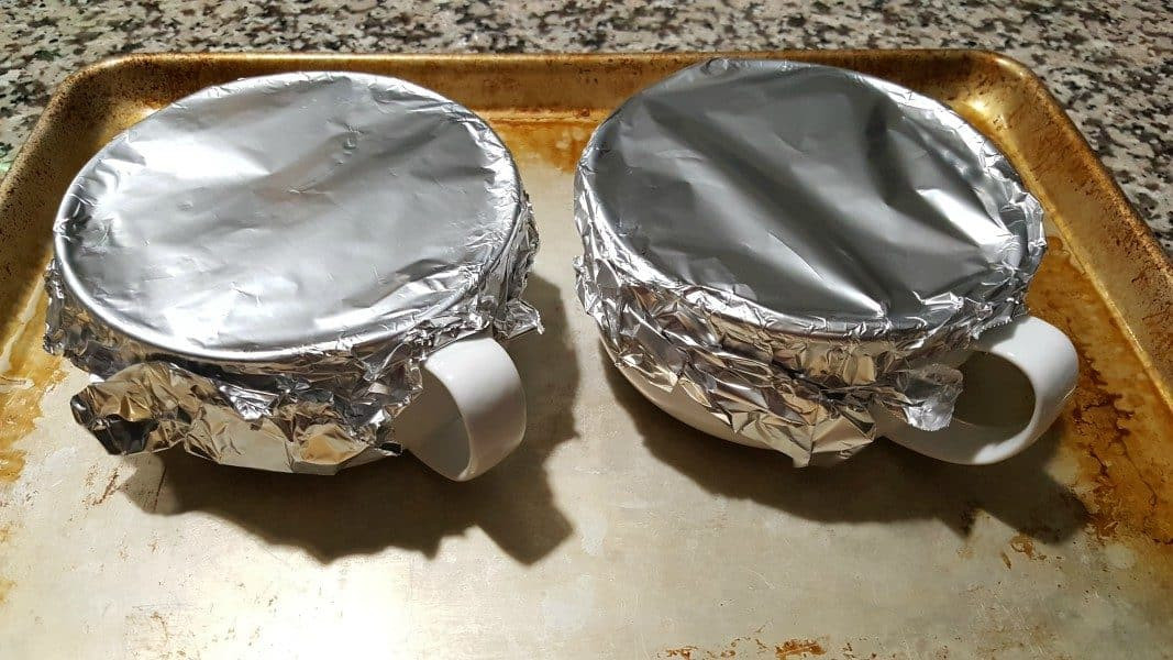 two baking dishes on a cookie sheet and covered with tinfoil