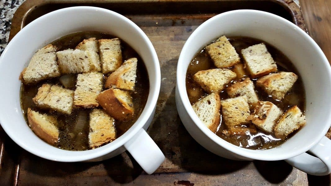 onion soup and croutons in two soup bowls