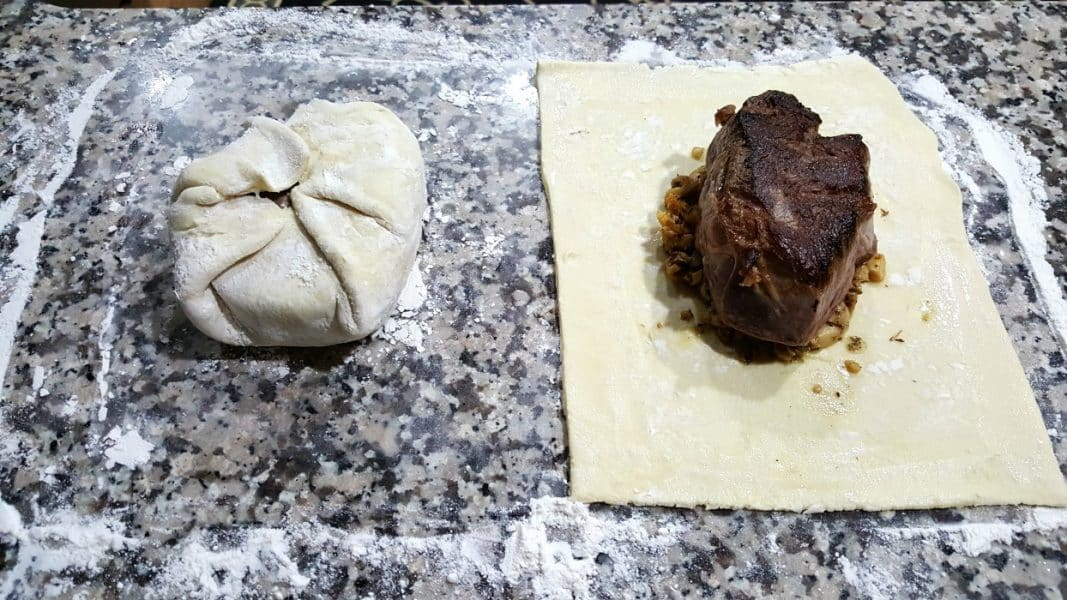 one beef tenderloin wrapped in puff pastry, one unwrapped on top of pastry