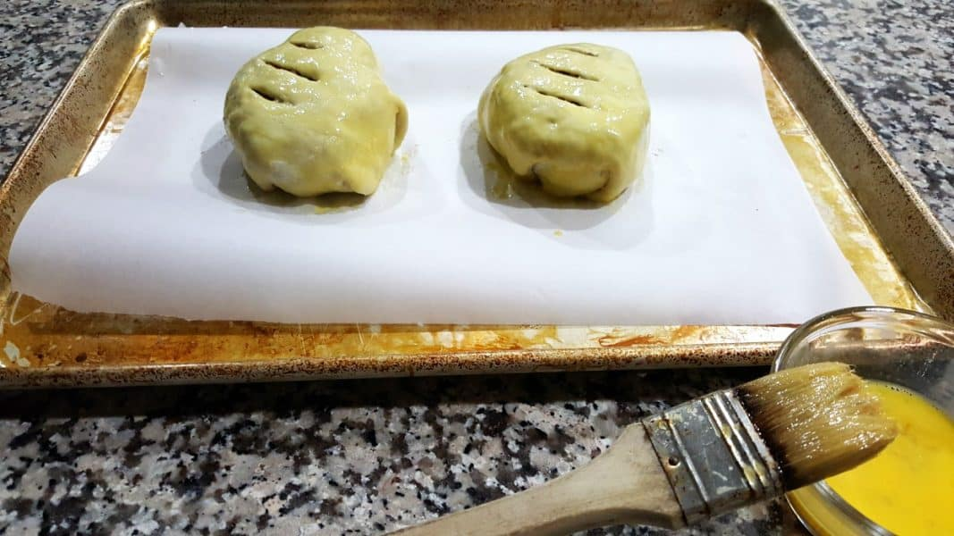 two uncooked beef wellington parcels brushed with egg wash