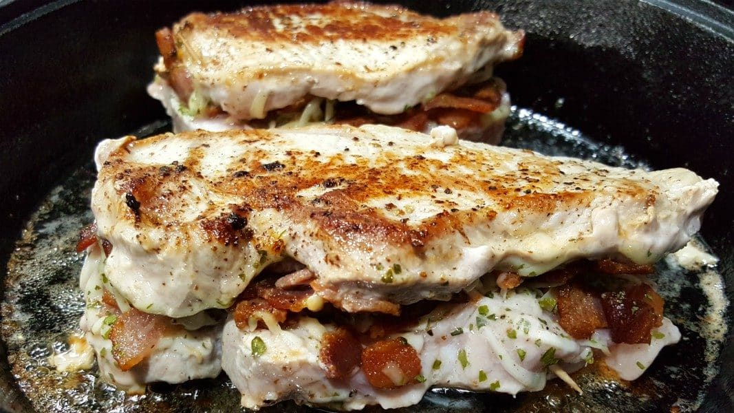 two stuffed pork chops browned on top frying in a cast iron skillet