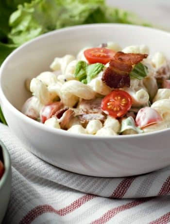a bowl of blt macaroni salad on a red and white striped towel with a bolw of cherry tomatoes and a pile of lettuce