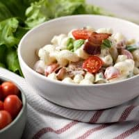 a close up of a bowl of blt macaroni salad on a red and white striped towel with a bolw of cherry tomatoes and a pile of green lettuce