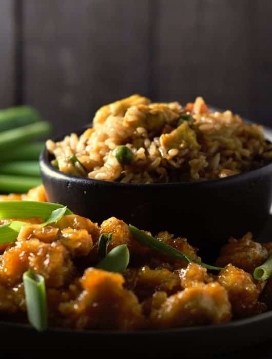 sweet and sour chicken topped with creen onions on a plate, fried rice in a bowl, chop sticks and green onions on the side