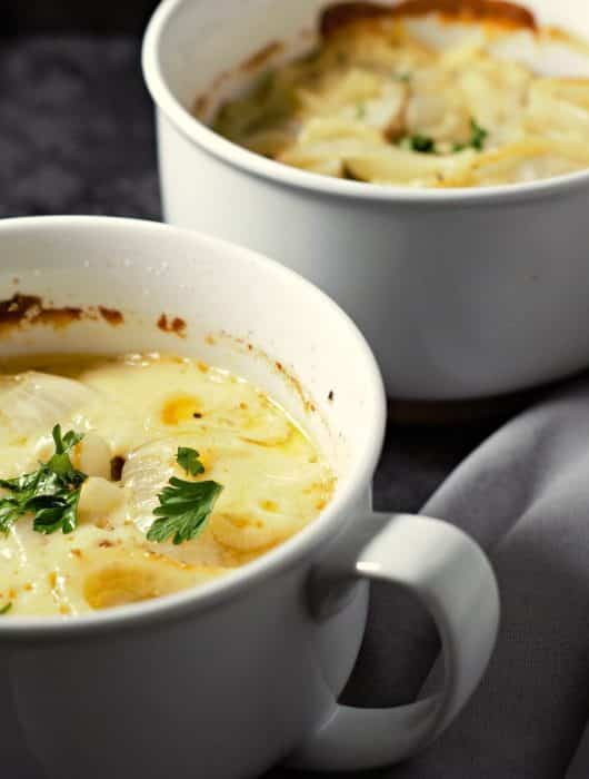 two bowls filled with cooked creamy au gratin potatoes