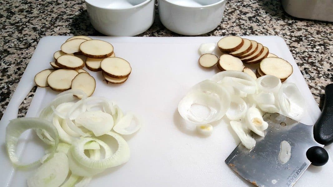 sliced potatoes, a knife, and sliced onions on a cutting board