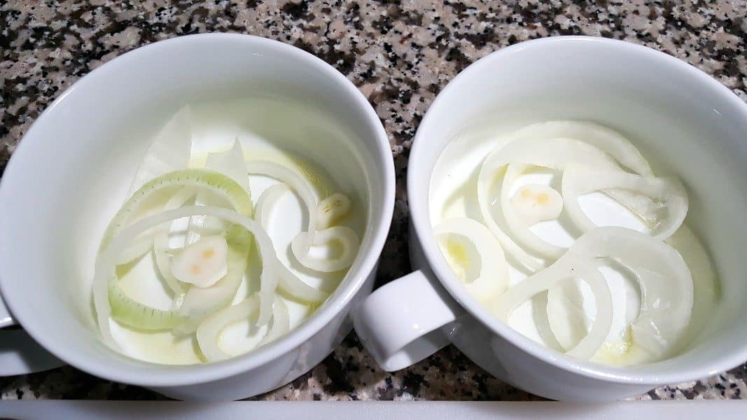 two bowls with sliced onions in the bottom