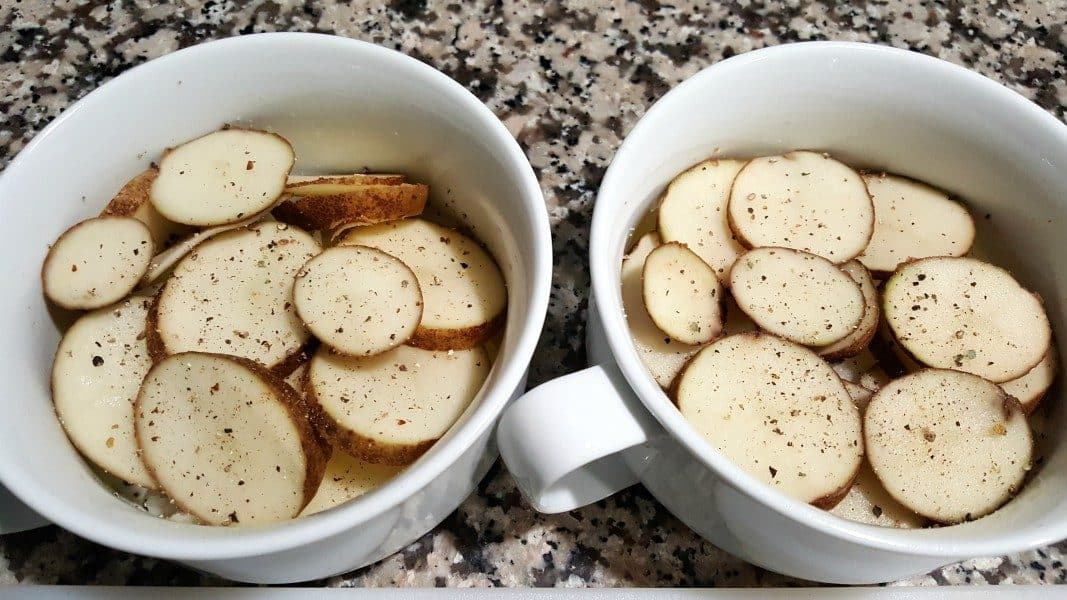 two bowls with sliced potatoes sprinkled with black pepper