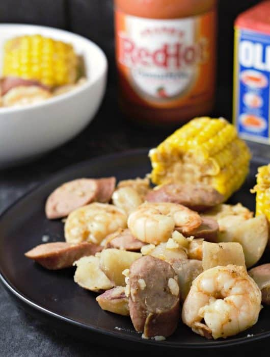 cooked cob corn, onion, potatoes, and smoke sausage on a plate and some in a bowl, a jar of hot sauce, and a can of old bay seasoning