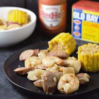 a close up of cooked cob corn, onion, potatoes, and smoke sausage on a plate and some in a bowl, a jar of hot sauce, and a can of old bay seasoning