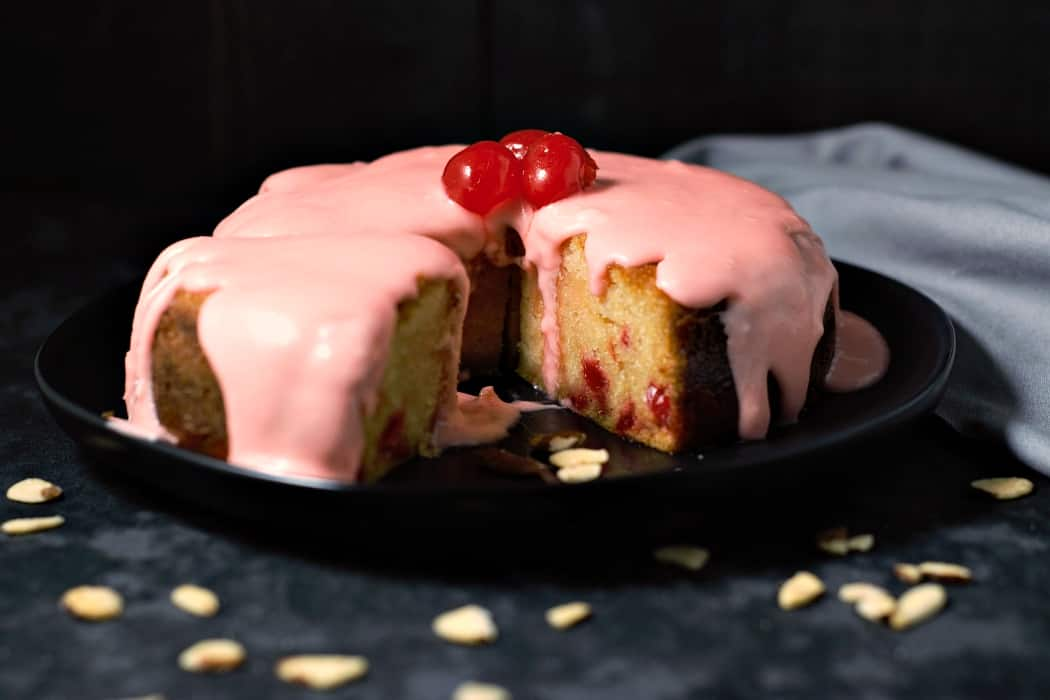 a glazed cherry almond cake on a plate with one slice cut and moved out a few inches