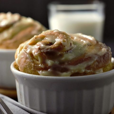 a close up of two cinnamon rolls in ramekins and a glass of milk