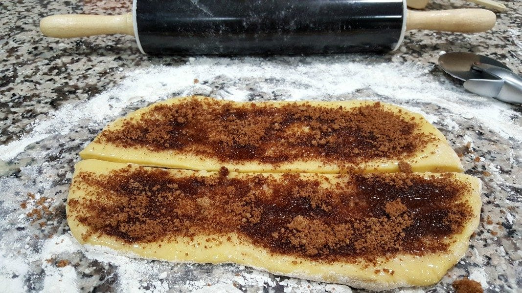 dough rolled out, cut in half, topped with butter and cinnamon sugar mixture