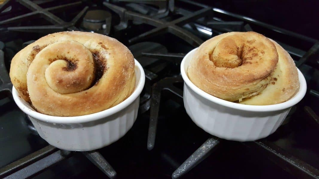 two ramekins filled with baked cinnamon rolls on a stove top
