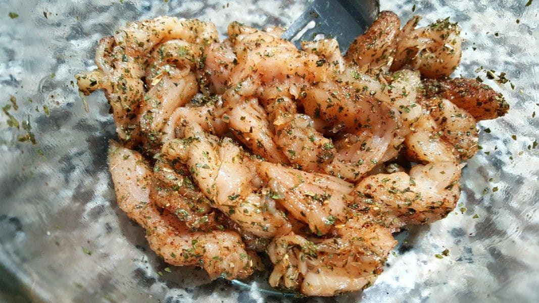 thin sliced chicken pieces coated in fajita herbs and spices in a bowl with a fork