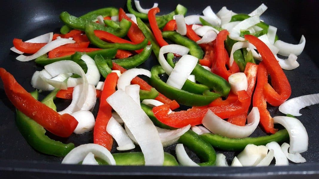 onion slices, green pepper slices, and red pepper slices in a frying pan