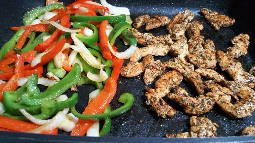 green pepper, red pepper, onion in a pile and fajita chicken in a pile, cooking in a frying pan