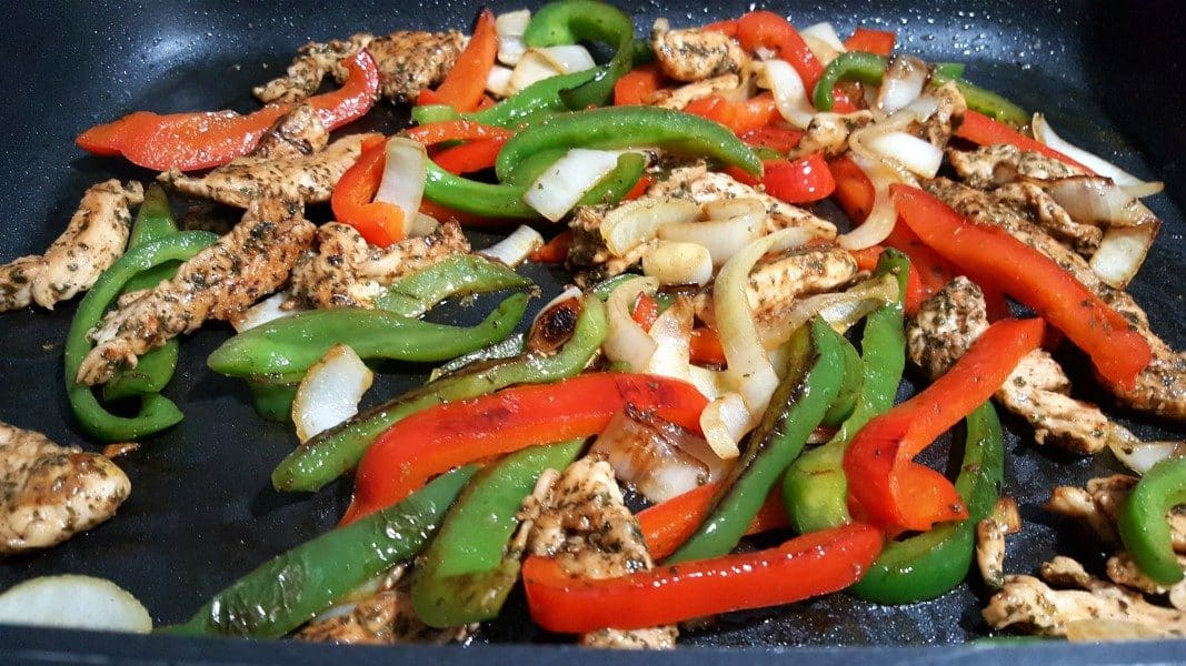 green pepper, red pepper, onion, and fajita chicken mixed together frying in a pan
