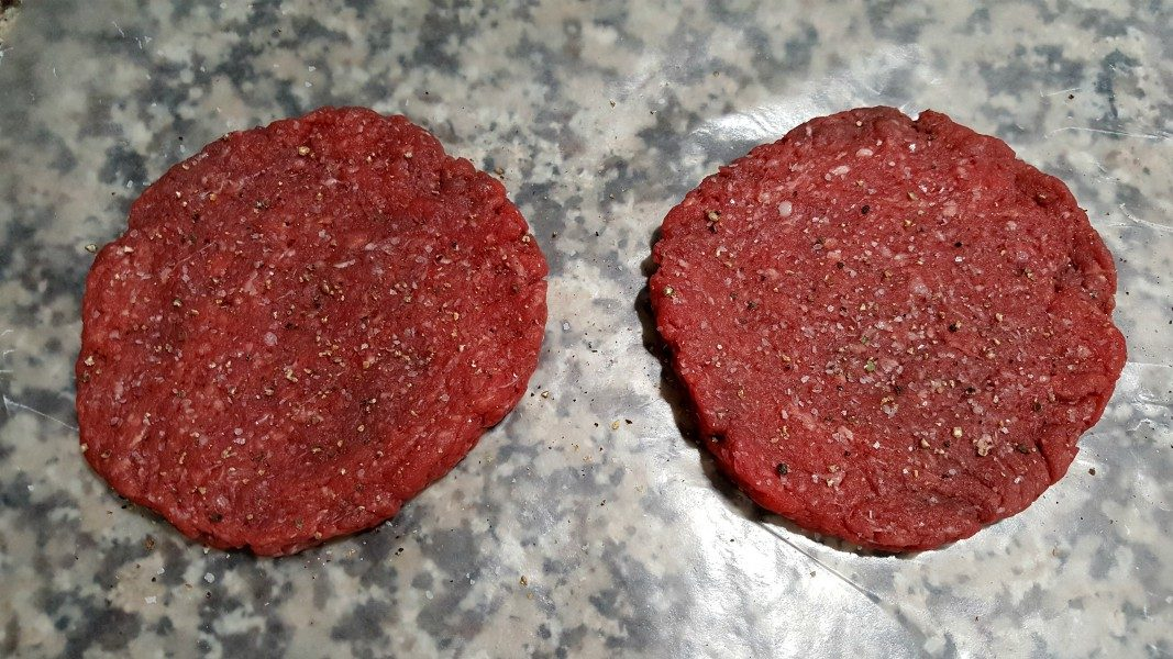 two perfectly round shaped raw beef patties sprinkled with salt and pepper