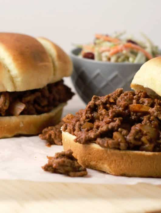 two sloppy joe sandwiches on a parchment lined cutting board and a bowl of coleslaw