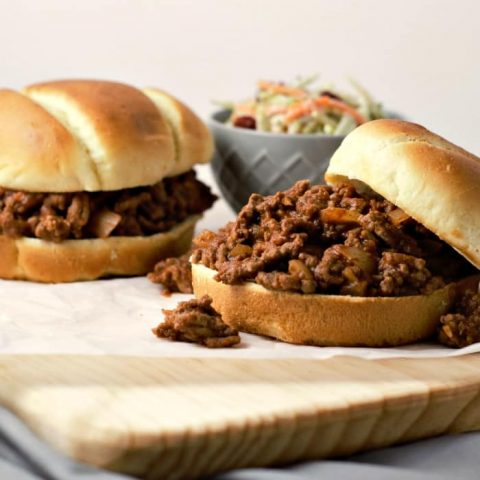 close up of two sloppy joe sandwiches on a cutting board and a bowl of coleslaw