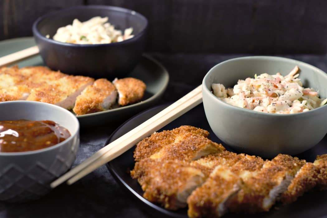 two plates, each with one breaded pork loin and a bowl of coleslaw and chopsticks, and a bowl with brown sauce on the side