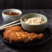a plate with a breaded pork loin, chopsticks, and a bowl of coleslaw on it, and a bowl on the side with brown sauce in it
