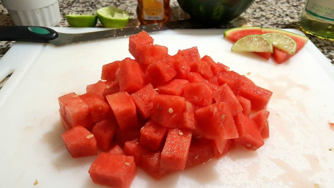 a pile of diced watermelon on a cutting board