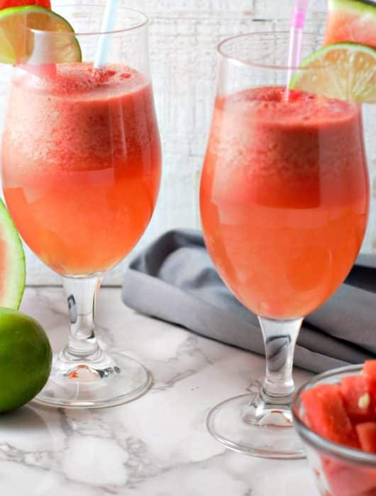 two glasses with pink watermelon sangria in them, watermelon and lime garnish slices and straws, with a watermelon slice and lime on the table, also a bowl of watermelon chunks and gray napkin