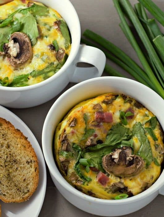 Baked Cheesy Ham Spinach Omelets in to dishes with toast and green onions on the side