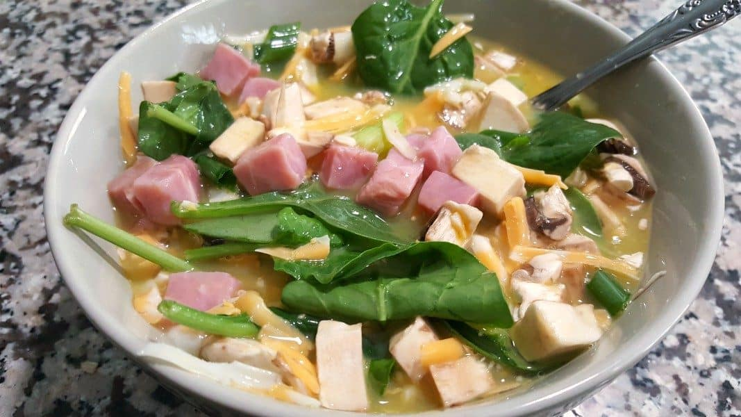 eggs, milk, salt, ham, spinach, mushrooms, cheese, and green onion mixed in a bowl with a spoon for baked omelets