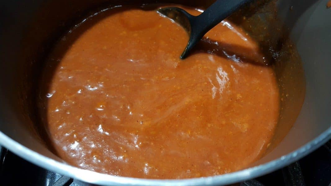 red wet burrito sauce cooking in a sauce pan