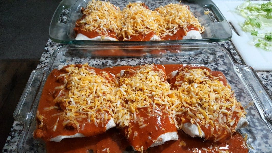 6 wet burritos covered in red sauce and shredded cheese