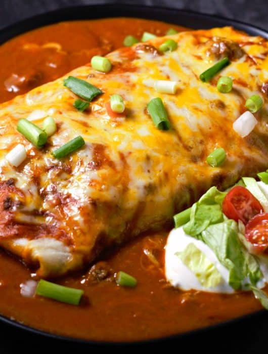 a burrito covered in red sauce, melted cheese, and green onions with a side dollop of sour cream topped with lettuce and tomato