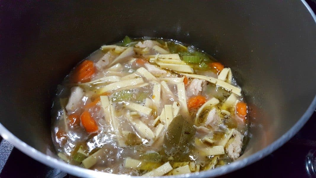 chicken noodle soup cooking in a large sauce pan