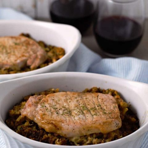 a close up of two baking dishes filled with stuffing topped with a pork chop next to two glasses of wine