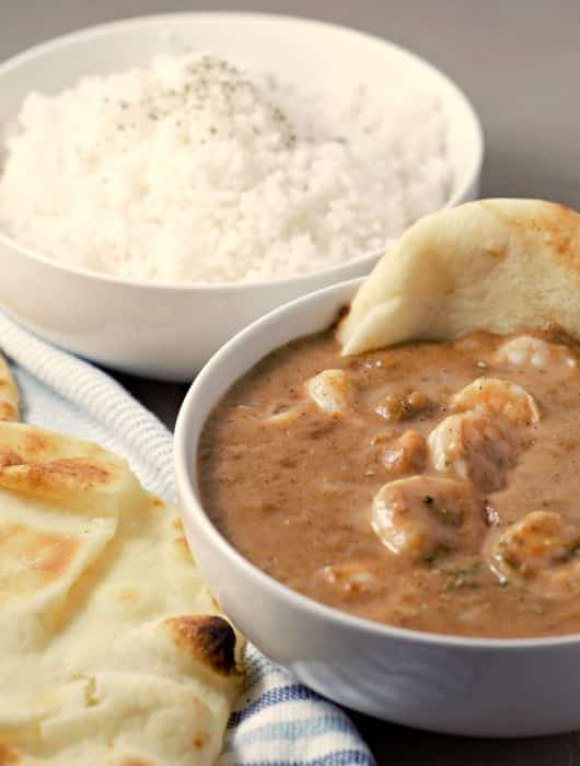 a bowl of shrimp korma, a bowl of white rice, and a side of naan bread