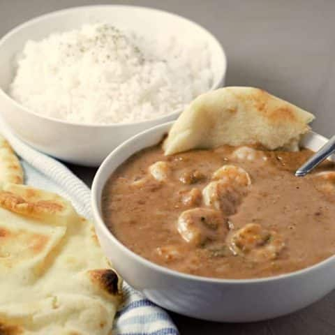 a close up of a bowl of shrimp korma, a bowl of white rice, and a side of naan bread